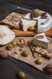 软制乳酪乳酪用核桃、蜂蜜和梨在土气桌上 免版税库存照片