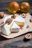 软制乳酪乳酪用核桃、蜂蜜和梨在土气桌上 免版税库存图片