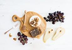 软制乳酪乳酪用葡萄,核桃、梨和蜂蜜在橡木服务上 免版税库存图片