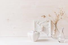 软的家庭装饰 贝壳和玻璃花瓶有小尖峰的在白色木背景 免版税库存照片