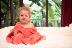 软的桃红色毯子的愉快的微笑的婴孩在白色床单在别墅卧室看照相机有被弄脏的热带的背景 库存照片