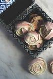 软的桃红色蛋白甜饼,被塑造象在一个蓝色框的玫瑰,开胃在情人节 免版税图库摄影