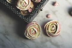 软的桃红色蛋白甜饼,被塑造象在一个蓝色框的玫瑰,开胃在情人节 免版税库存图片