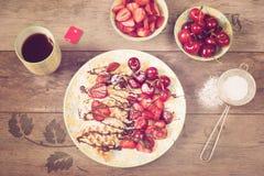 软的比利时心形的奶蛋烘饼用樱桃和草莓、巧克力顶部和搽粉的糖在黄色板材 红茶, 免版税库存图片