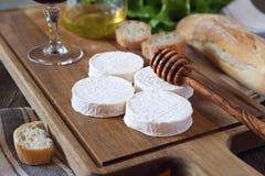 软的法国山羊乳干酪、面包、蜂蜜、莴苣和葡萄酒杯 图库摄影