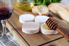 软的法国山羊乳干酪、面包、蜂蜜、莴苣和葡萄酒杯 库存照片