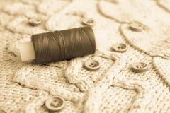 软的温暖的自然毛线衣、织品与毛线的一个被编织的样式和红色小圆的按钮缝合的和红色螺纹丝球  免版税库存图片