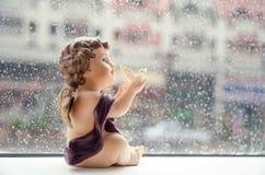 软的焦点举行白色的一名小的丘比特在雨背景潜水树脂 免版税库存照片