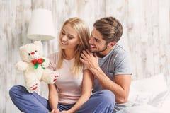 给软的玩具的愉快的丈夫妻子 免版税库存照片