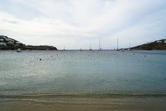 软的风景美好的海景和自然沙子靠岸与帆船、清楚的天空、山和白色大厦背景, Ornos 库存照片
