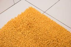 软的黄色地毯在一个白色瓦片说谎 免版税图库摄影