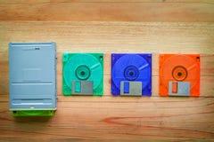 软盘驱动器和磁盘在木桌上 免版税图库摄影