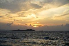 软绵绵地宽橙色和蓝色日落颜色天空和抽象云彩背景美丽的树荫与有风波浪seaview 库存照片