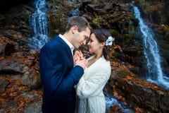 软软地握手的年轻婚礼夫妇 在背景的惊人的瀑布 库存图片