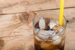 软饮料,与冰块的可乐玻璃在木背景 图库摄影