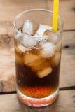 软饮料,与冰块的可乐玻璃在木背景 库存照片
