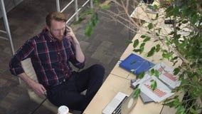 轰烈有胡子的人坐椅子和谈话在电话 影视素材