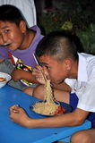 轰隆Saen,泰国:吃面团的男孩 库存照片