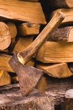 轴在反对在平的堆的切好的木柴背景的一本日志被困住  免版税库存照片