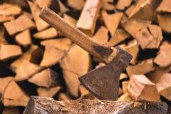 轴在反对在平的堆的切好的木柴背景的一本日志被困住  免版税库存图片