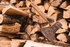 轴在反对在平的堆的切好的木柴背景的一本日志被困住  免版税图库摄影