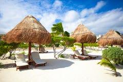 轻便马车休息室在沙滩的一把伞下 免版税库存照片