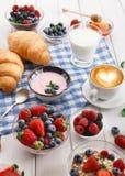 轻快早餐用新月形面包和莓果在方格的布料 免版税图库摄影
