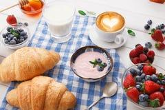 轻快早餐用新月形面包和莓果在方格的布料 图库摄影