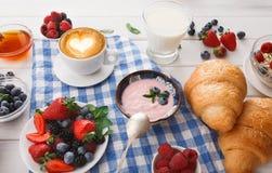 轻快早餐用新月形面包和莓果在方格的布料 库存图片