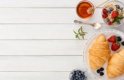 轻快早餐用新月形面包和莓果在白色木头 免版税图库摄影