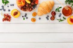 轻快早餐用新月形面包和莓果在白色木头 免版税库存照片