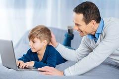 轻拍他的儿子的头爱恋的父亲使用膝上型计算机 免版税图库摄影