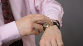 轻拍他的手表和检查时间,打破的机械手表的男性 股票视频