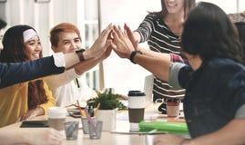 轻拍手/喂fiving在协议的小组businesspersons在会议 库存照片