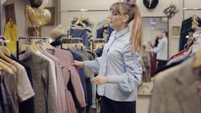 轻易获胜T恤杉的年轻俏丽的女推销员,当设法她的女性的客户找到自己一些新的衣裳时 影视素材