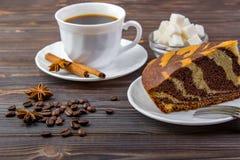 轻松的事与一杯咖啡的 肉桂条、茴香、叉子和一个碗有糖立方体的在黑暗的木背景 图库摄影