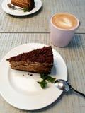 轻松的事在一块白色板材的在一个咖啡馆的一张桌上在一杯咖啡热奶咖啡附近 免版税库存照片