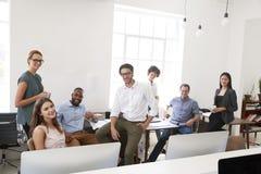 轻松的企业同事在他们的办公室微笑对照相机 免版税图库摄影