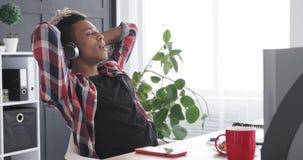 轻松的使用耳机的商人唱歌的和听的音乐在办公室 影视素材