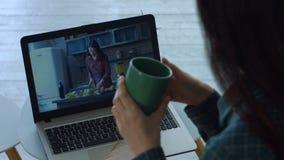 轻松的在膝上型计算机个人计算机的妇女观看的录影在家