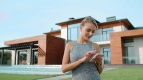 轻松的在豪华房子附近的妇女短信的机动性 在别墅附近的俏丽的妇女身分 股票视频