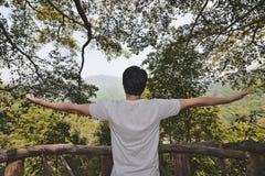 轻松的年轻亚洲人背面图有胳膊的扩大了身分反对绿色自然 免版税库存照片