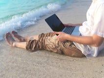 轻松的年轻亚裔人的播种的图象有膝上型计算机的坐热带海滩沙子在假日 图库摄影