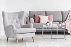轻松的扶手椅子和灰色沙发有桃红色枕头和咖啡桌的 库存照片
