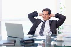 轻松的生意人与膝上型计算机一起使用 免版税库存照片