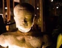轻松的石菩萨雕象在晚上照亮了与灯 库存图片