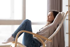 轻松的镇静在舒适的摇椅的年轻女人lounging开会 免版税库存图片
