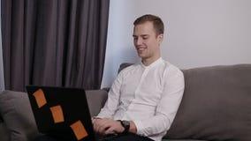 轻松,微笑的年轻人在家坐研究膝上型计算机的沙发 愉快的心情,自由职业者 有现代的室 影视素材
