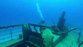 轻潜水员探索一艘凹下去的巡逻艇的击毁 股票视频