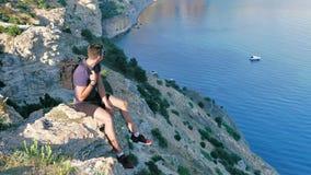 轻率冒险体贴的男性背包旅客坐享用白色船的峭壁在清楚的蓝色海 影视素材